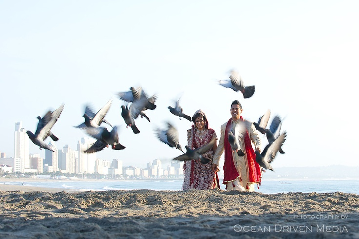 Bride and groom on beach chasing pigeons