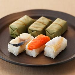 """Kakinohazushi: pressed sushi (oshizushi) wrapped in a persimmon leaf. (Kaki = persimmon, ha = leaf.) """"A regional product of Nara and Wakayama prefectures. Usual toppings are saba (mackerel), sake (salmon), and tai (sea bream). Oshizushi (pressed sushi) are popular in the Kansai area. The sushi are wrapped individually in persimmon leaves, a way to preserve the sushi in the Edo-period. Sometimes the sushi are first wrapped in konbu."""""""