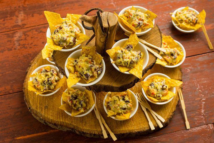 Verwarm de oven voor (180 graden). Smeer 4 kleine (ovenbestendige) schaaltjes in met een klein beetje olijfolie. Breek de nacho chips in kleinere stukjes en snij de paprika zo fijn...