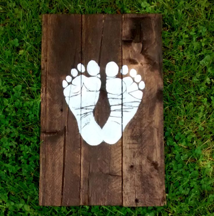 This idea for nursery wall decor is so sweet! Their little footprints painted in white on a stained pallet wood sign.
