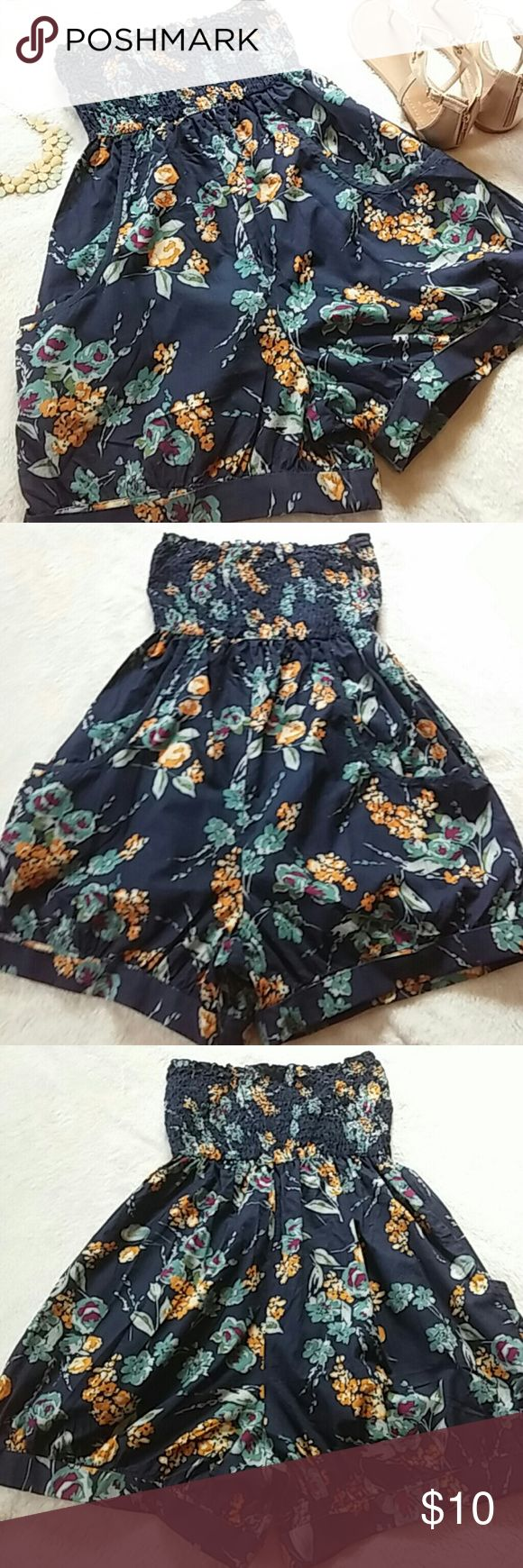 """Strapless Floral Romper Cute navy colored, strapless romper with an all over floral pattern. The floral design is in shades of gold, teal, gray and purple. Smocked tube top. Side pockets. Cuffed legs. 23"""" long. 100% cotton. Excellent condition. Xhilaration Shorts"""