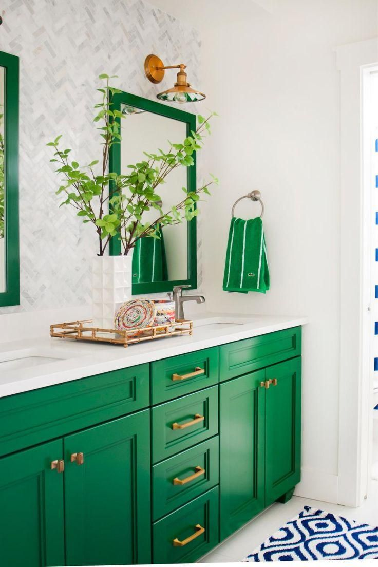 This gorgeous green-and-white bathroom is a preppy dream! Two mirrors and a double vanity make it easy for a pair of people to prepare for their day. Farmhouse-style fixtures light up the space, while a blue-and-white throw rug provides a bright contrast to the kelly green cabinets and accents.