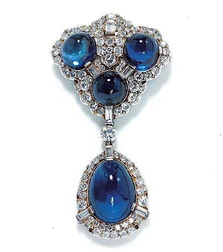 AN ART DECO CABOCHON SAPPHIRE, DIAMOND AND PLATINUM PENDANT BROOCH     BROCHE PENDENTIF   en platine et or gris, triangulaire festonnée retenant un motif piriforme, le premier orné de trois cabochons, le second d'un cabochon de saphir, les encadrements sertis de diamants taillés en brillant coupés de diamants taillés en baguette.   Époque 1930.   Poids des saphirs : env. 17 cts