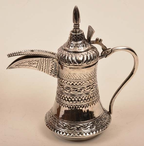 Small Middle Eastern coffee pot of ewer form with elongated curved spout and domed hinged lid surmounted by slender finial and with scrolling handle to side, decorated with geometric banding #ukauctioneers