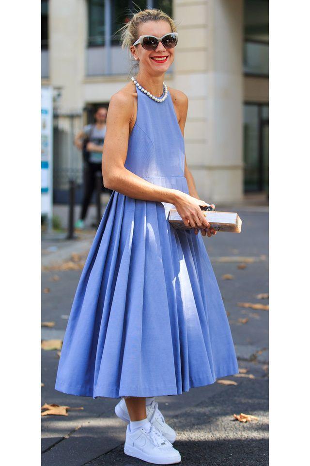 Une robe longue en jean très évasée style 60s revisité avec un collier en perles, des baskets blanches et des lunettes style 60s.