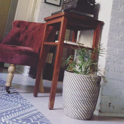IKEA plant and basket, Urban Outfitters rug, World Market chair, thrifted table and typewriter.