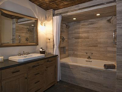 Marble encased, two-person soaker tub with double shower heads.