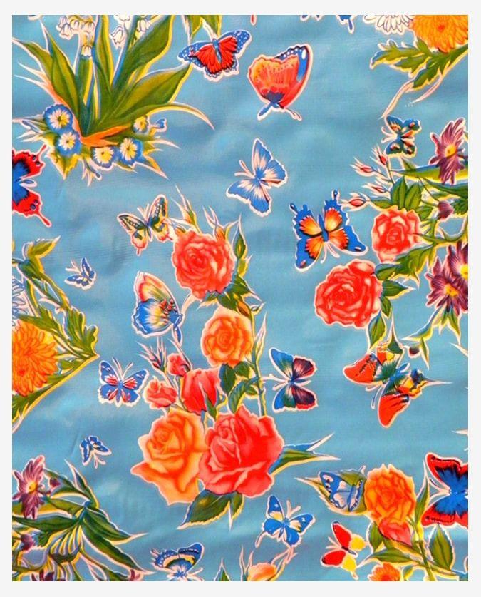 Toile cirée mexicaine très colorée à motifs fleurs et papillons fond bleu ciel. Nappe,déco, DIY, confection. Vendue au mètre linéaire par 120cm de large.