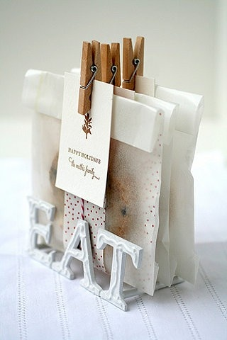 Mini clothespins securing a gift tag on individually wrapped cookies.