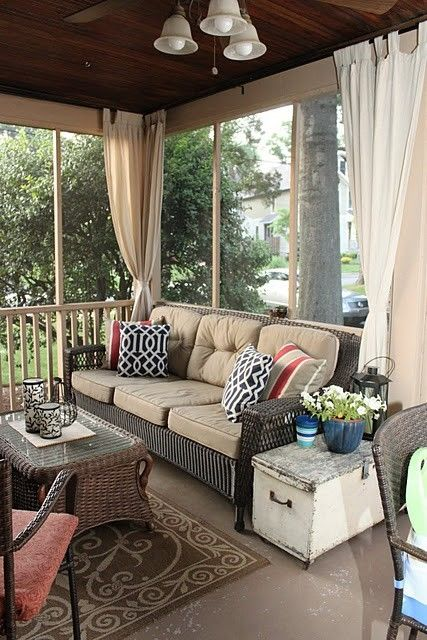 Cozy screened in porch with curtains.