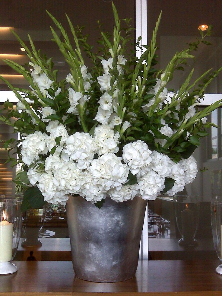 BEAUTIFUL, LOTS OF FULL HYDRANGEAS AND TALL GLADIOLI AND BRUSHED ALLUMINIUM CONTAINER. AGAIN YOU DON'T HAVE TO HAVE IT THIS BIG.