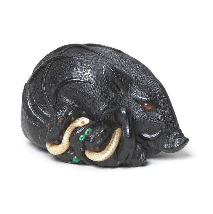 A black wood and ivory netsuke of a boar and snake
