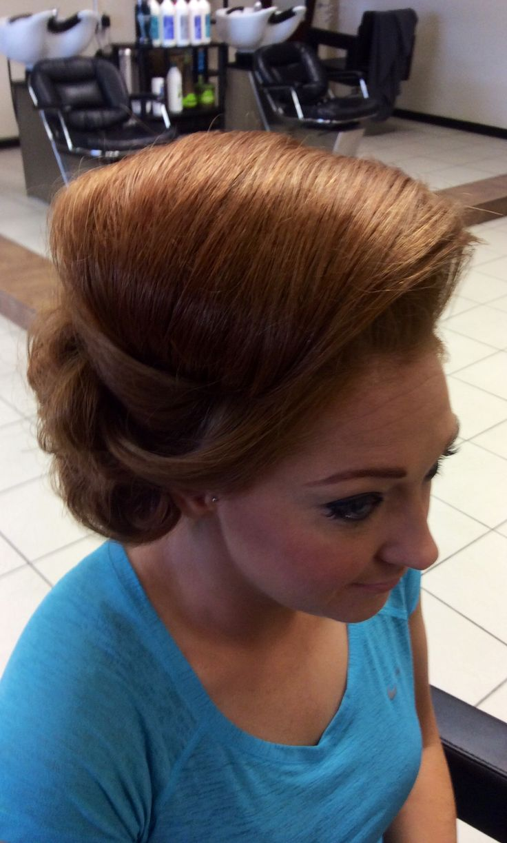 Large bump with hair twisted underneath at front and sculpted detail behind right ear, perfect wedding hair