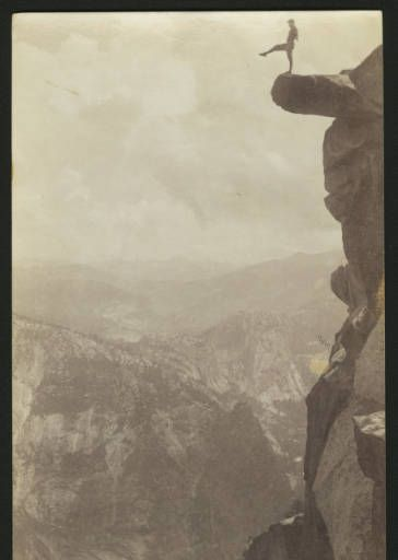 Man posing on one leg on an overhanging rock at Glacier Point in Yosemite National Park, ca.1920-1930 :: California Historical Society Collection, 1860-1960