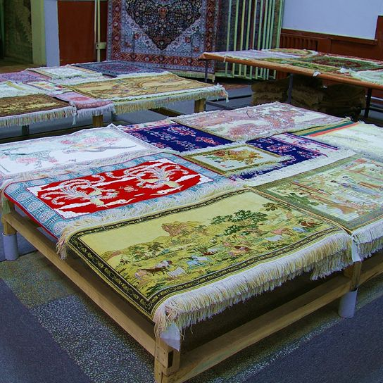 Silk carpets cover the tables in a showroom in Kashgar.