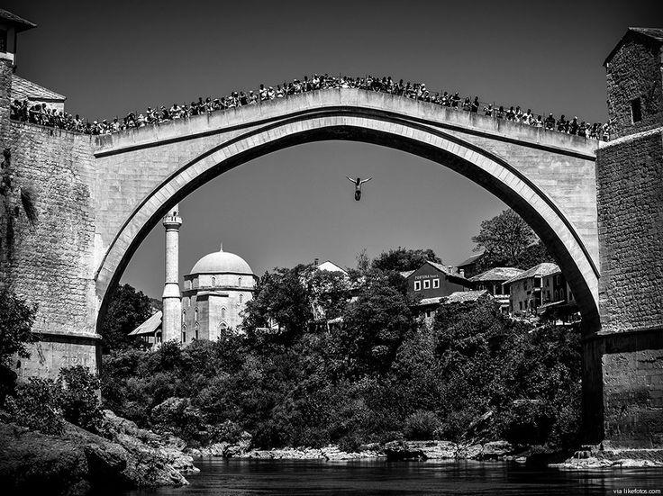Fotografia a preto e branco plenamente enquadrada com mergulhador que salta dos 25 metros de altura da Ponte Old Mostar, no rio Neretva, Bósnia.
