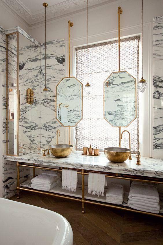 Une salle de bain alliant le marbre et le doré or aux allures rétro