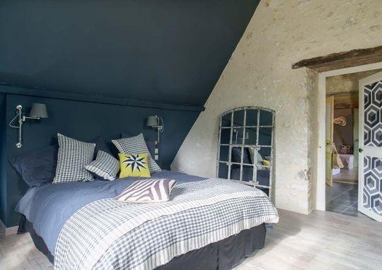 Chambre sous les combles avec un mur en pierre. Plus de photos sur Côté Maison http://petitlien.fr/7j36