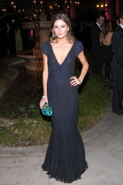 Vestido simples preto longo para convidadas de casamentos, com clutch verde para dar cor ao look. Na foto, Olivia Palermo.