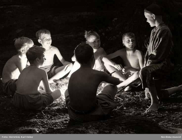 En grupp pojkar runt lägereld på Skå barnkoloni, Ekerö, Uppland @ DigitaltMuseum.se