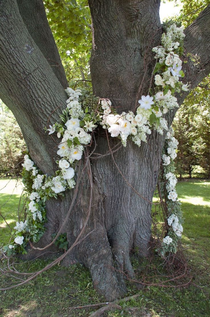 This will be done in the two groupings of trees (one on left and one on right) just past the fence that the wedding party walks through to begin their walk down the aisle. We will use seeded eucalyptus white lilies white alstromeria babys breath queen annes lace and amaranthus .
