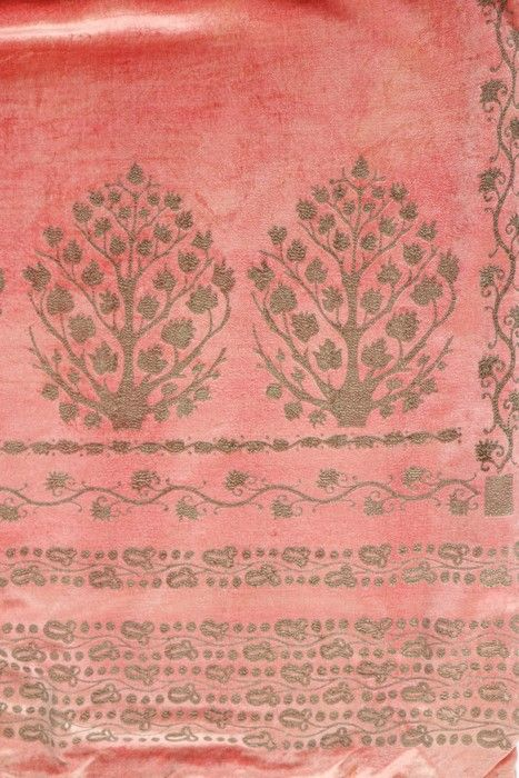 A Mariano Fortuny stencilled pink velvet mantle, circa 1920. bearing circular label to lining, printed in gold with scrolling vine and stylised tree motifs, with side slits forming armholes .