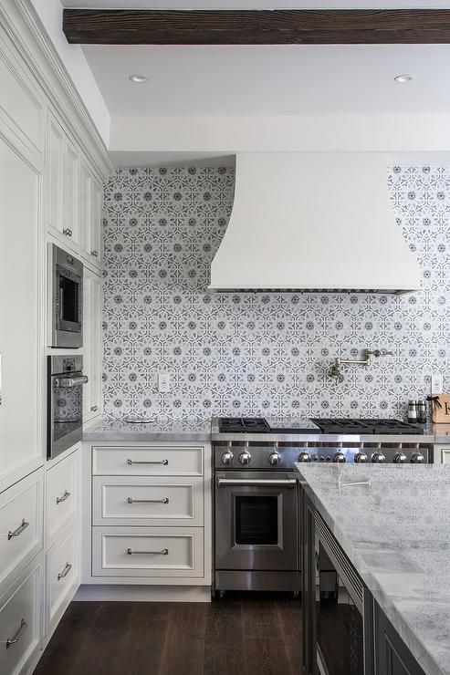 Ivory and gray kitchen features ivory shaker cabinets paired with marble countertops and a gray flower mosaic tiled backsplash, Walker Zanger Villa d'oro Collection Granada Decorative Field in Grigio.