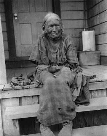 Nez Perce woman named Chica-ma-poo and known as Old Jean sits on porch steps of wooden house, Colville Indian Reservation, Washington, ca. 1903. :: American Indians of the Pacific Northwest -- Image Portion
