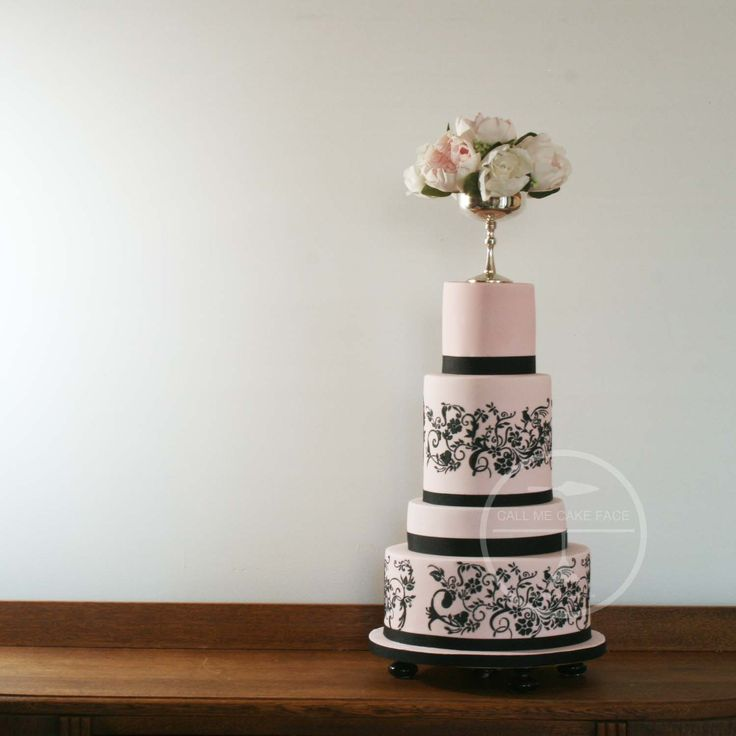 Pale pink wedding cake with black lace detail.  Goblet topper of sugar peonies.