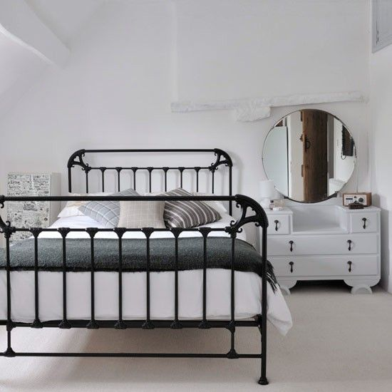 A decorative iron bed painted in matte black - despite some moldings, this looks more industrial than romantic