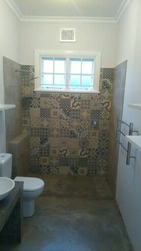 Unmatched tiles as a feature wall in the shower area and cement screeded floors and countertop.