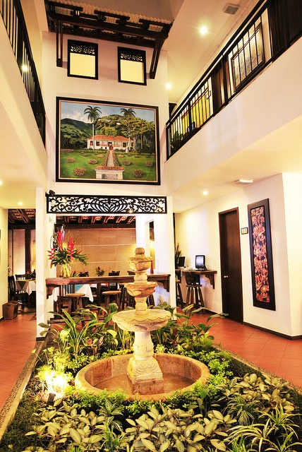 """Una de nuestras locaciones interiores decorada con una bella fuente y una obra maestra del artista LUIS EMILIO RENTERIA """"la Hacienda el Paraíso"""" la cual sobresale en la decoración."""