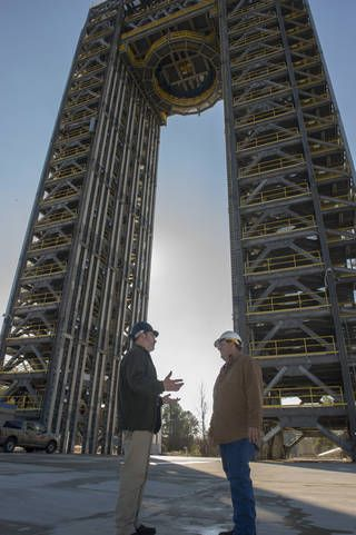 Robert Bobo, left, and Mike Nichols talk beneath the 221-foot-tall Test Stand 4693.