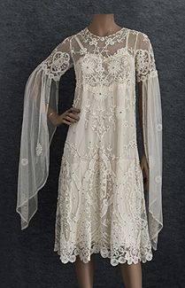 Appliquéd princess lace wedding dress, c.1925. Lavishly embellished with princess lace appliqués, faux pearls, and rhinestones, this endearing dress comes with the original slip, which has a finely detailed lace bodice that shows through the dress. For a period-themed wedding, you can wear it as is. For a more casual flapper style, you can remove the long lower sleeves.