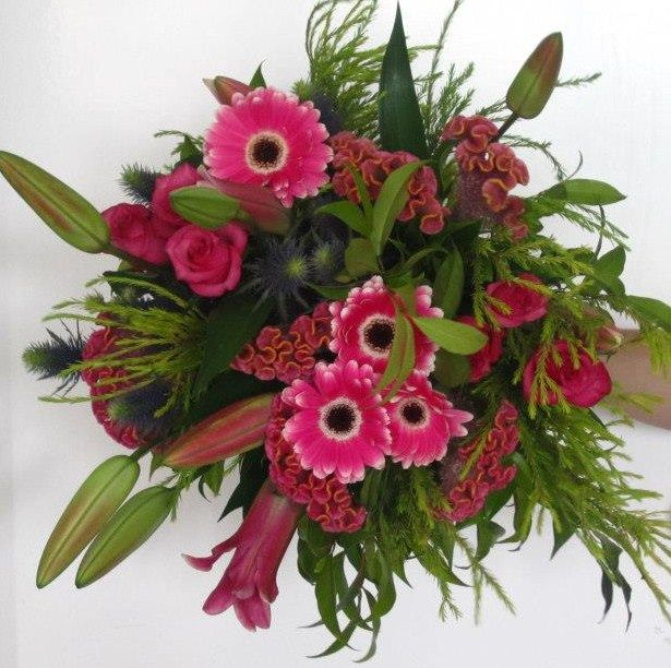 This lush bouquet speaks of gentle love with teh vibrant hot pink roses and mix of seasonal flowers.