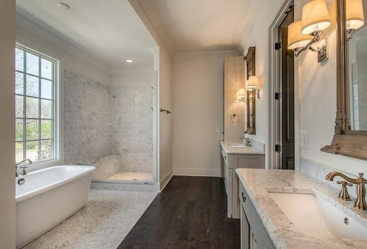 Black double doors open to a long bathroom boasting separate gray washstands topped with gray and white marble countertops under neoclassical window mirrors, Restoration Hardware Trumeau Mirrors, illuminated by Restoration Hardware Campaign Double Sconces.