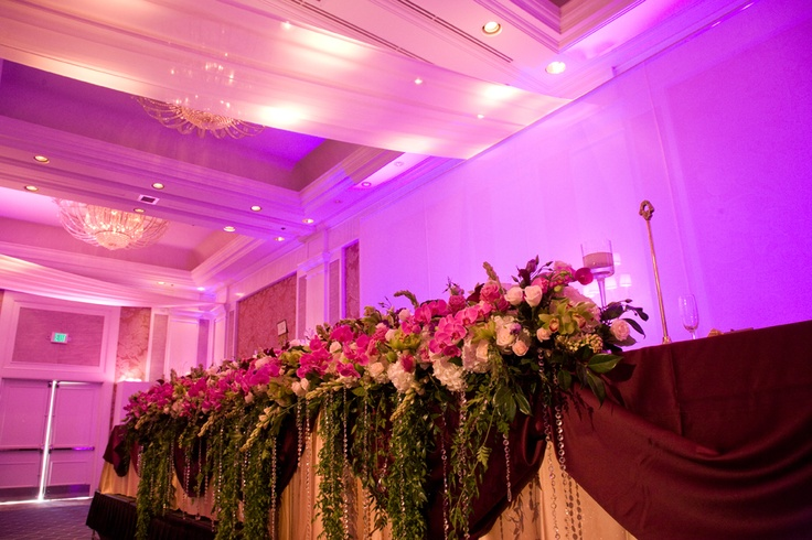 The traditional head table looks not-so-traditional with panels of fabric stretched above and luxurious flowers cascading down its front.  Photo by Sieber Studio.