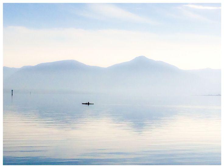 Kajakk på blikkstille hav med Malangsfjell som bølger.
