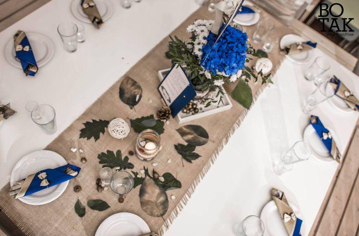 Rustykalne, granatowo - złote jesienne wesele. Biało-niebieskie kwiaty w słoiku z koronką, obok menu, ekologiczny bieżnik, złote liście, szyszki, żołędzie i kamyczki. Na talerzach sztućce w złotych i granatowych serwetkach, obwiązane sznurkiem z koronkową kokardką. / Rustic, wedding, natural, eco, table, decoration, fall, autumn, ideas, white, gold, navy, blue, flower, centerpieces, rocks, cones, acorns, leaves, candles, mason jar, lace, table number, menu.