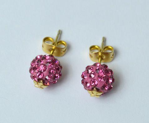 Κωδικός 8986:Τα σκουλαρίκια αποτελούνται από κεραμικές χάντρες με στράςς σε ροζ και χρυσές διακοσμητικές λεπτομέρειες.