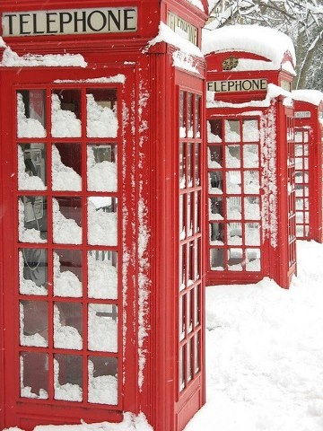 Iconic British phone booths in snow.