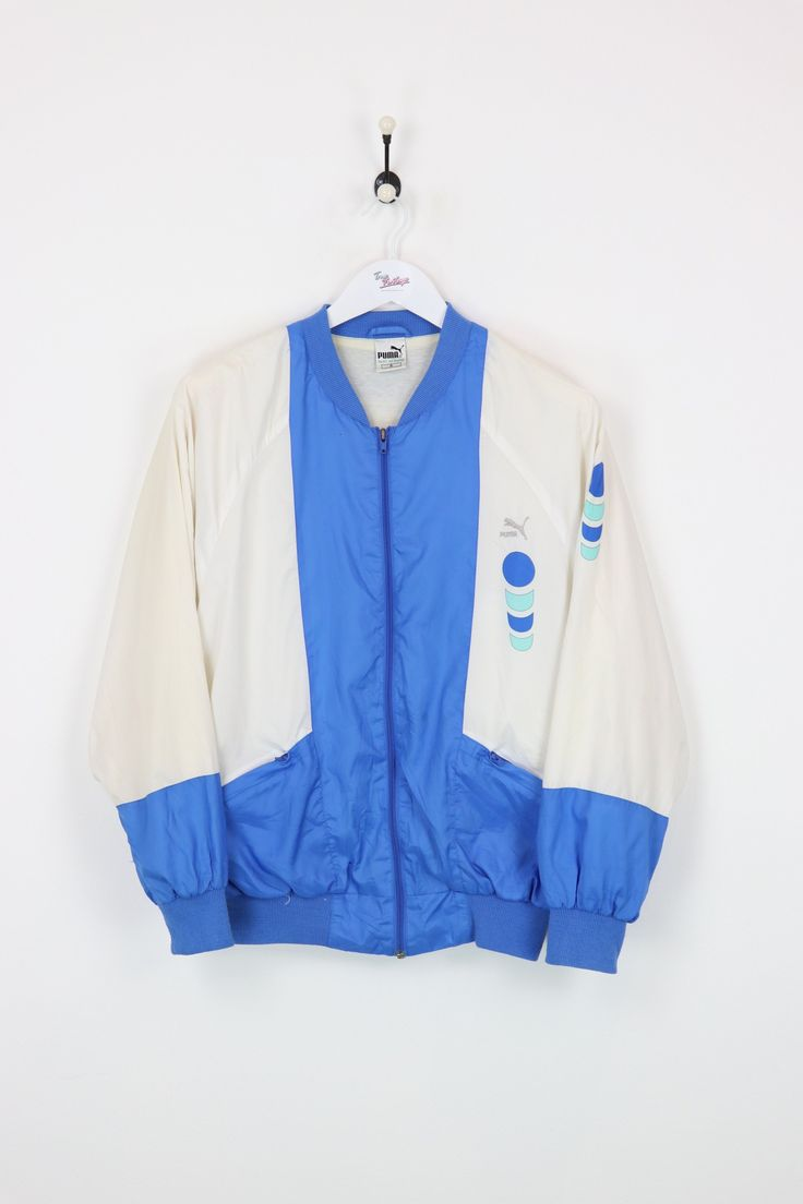 "Puma Shell Suit Jacket White/Blue Medium :  Vendor: PumaType: Jackets & CoatsPrice: 27.00  Very good condition apart from small hole on the outer lining (does not go all the way through). Vintage Puma shell suit jacket.  Measurements:  Pit to Pit - 23""  Length of back - 26""  Vintage items will usually show a few signs of wear or fading but anything substantial will be noted.  For any further information on this item please use the contact form and we will be happy to help."