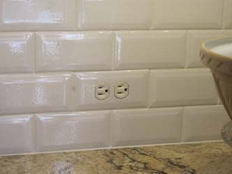 Close up of a tiled in subway tile switch plate cover. Definitely doing this to hide all the ugly outlets required by current code. DIY?