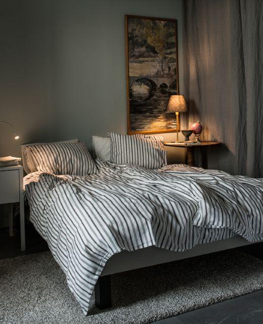 Soverom i lyse farger med seng og to nattbord.