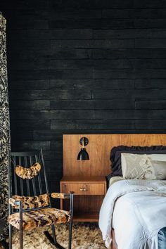 HGTV invites you to see this dynamic master bedroom with a charred, reclaimed wood accent wall and midcentury modern furniture.