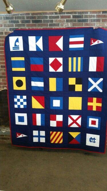 Nautical flag quilt with four corner blocks.