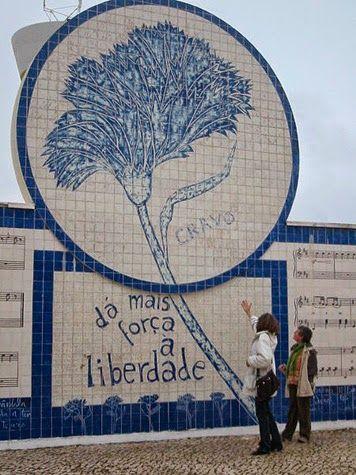 """MEMORIAL AO 25 DE ABRIL - monumento representativo do 25 de Abril situado na entrada noroeste da vila alentejana de Grândola. Marcado pelo revestimento em azulejo dominantemente de cores azul e branca, pode ler-se no painel central do monumento a frase """"Dá mais força à Liberdade"""", o desenho de um cravo e a pauta musical da música """"Grândola, Vila Morena""""."""