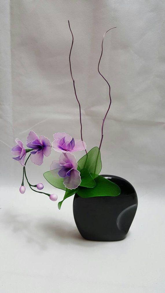 Media flor en florero negro de nylon. Flor de color púrpura.