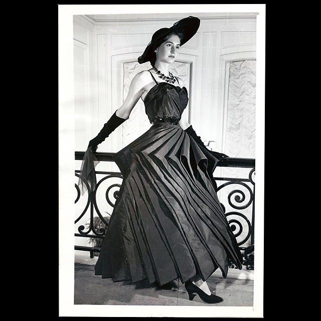 "An original 1948 print showing Christian Dior's Cyclone dress. 30 yards of black taffeta were used for the skirt! A spectacular look in the postwar years. Cyclones were apparently an inspiration for couturiers as Jeanne Lanvin already designed a Cyclone dress in 1939 (as posted today by @the_art_of_the_dress ). The caption of our print reads: ""Let a skirt be your umbrella. Christian Dior, originator of the new look, comes forth with a sensationally different evening gown that uses no less…"