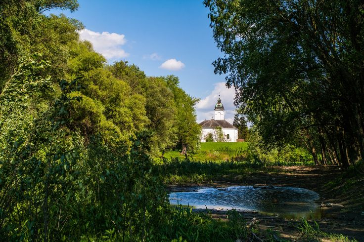 Church near the River - A church close to the Danube river, taken from the side of a small bay surrounded by trees. The bay is currently not connected to the river due to lower water levels.